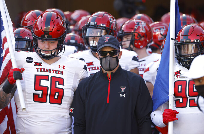 Texas Tech head coach Matt Wells and his team including Texas Tech offensive lineman Jack Anderson (56) and Texas Tech defensive lineman Jaylon Hutchings (95) wait before playing TCU in an NCAA college football game Saturday, Nov. 7, 2020, in Fort Worth, Texas. (AP Photo/Ron Jenkins)