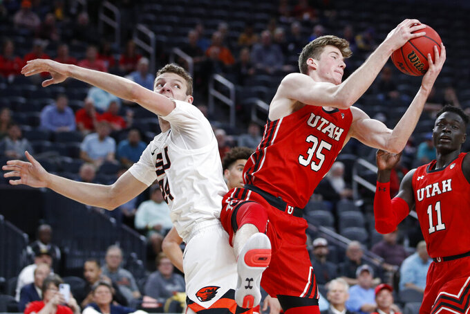 Utah's Branden Carlson (35) grabs a rebound over Oregon State's Kylor Kelley during the first half of an NCAA college basketball game in the first round of the Pac-12 men's tournament Wednesday, March 11, 2020, in Las Vegas. (AP Photo/John Locher)