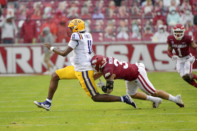 LSU quarterback TJ Finley (11) tries to get away from Arkansas defender Grant Morgan during the second half of an NCAA college football game Saturday, Nov. 21, 2020, in Fayetteville, Ark. (AP Photo/Michael Woods)