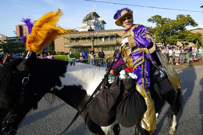 """A horse and rider lead off a parade dubbed """"Tardy Gras,"""" to compensate for a cancelled Mardi Gras due to the COVID-19 pandemic, in Mobile, Ala., Friday, May 21, 2021. (AP Photo/Gerald Herbert)"""