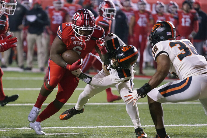 Utah running back Devin Brumfield (6) is tackled by Oregon State defensive back Akili Arnold (0) during the first half of an NCAA college football game Saturday, Dec. 5, 2020, in Salt Lake City. (AP Photo/Rick Bowmer)