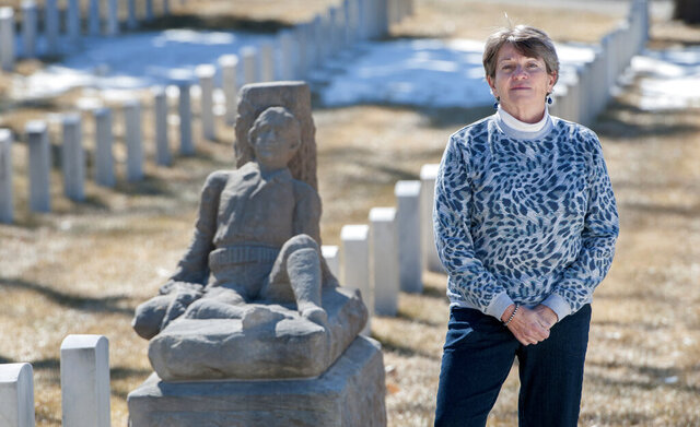 """In this Feb. 26, 2020, photo, author and historian Ana Pacheco stands near the sculpture of Dennis O'Leary, who created his own tombstone, in the Santa Fe National Cemetery. The author of several books about New Mexico history, Pacheco's latest effort is """"New Mexico Death Rituals,"""" published in late-2019 by The History Press of Charleston, S.C. (Eddie Moore/The Albuquerque Journal via AP)"""