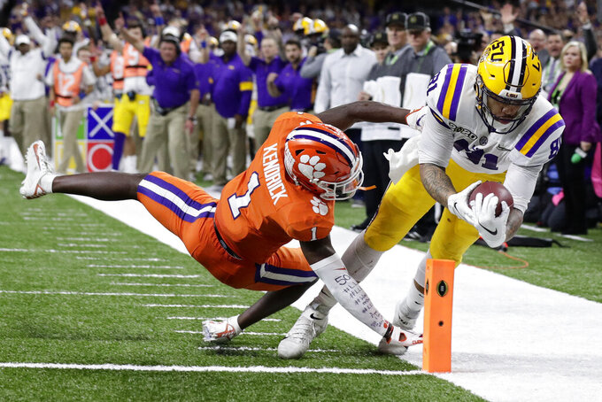 LSU tight end Thaddeus Moss scores a touchdown past Clemson cornerback Derion Kendrick during the second half of a NCAA College Football Playoff national championship game Monday, Jan. 13, 2020, in New Orleans. (AP Photo/Sue Ogrocki)
