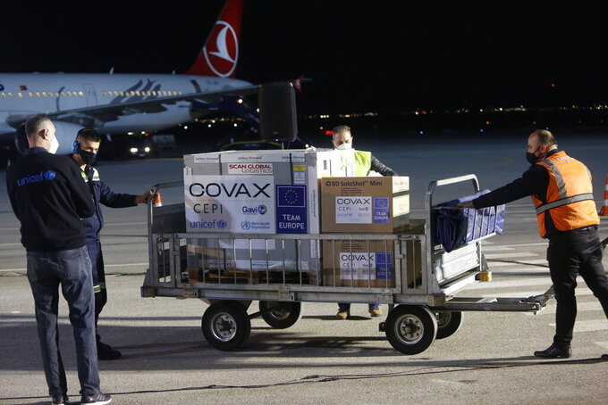 FILE - In this Sunday, March 28, 2021 file photo, airport personal unload the first batch of the AstraZeneca vaccines sent from the Covax facility, at Adem Jashari airport Pristina, Kosovo which is the last country in the continent yet to start inoculations. In late June, the international system for sharing coronavirus vaccines sent about 530,000 doses to Britain – more than double the amount sent that month to the entire continent of Africa. It was the latest example of how a system that was supposed to guarantee low and middle-income countries vaccines is failing, leaving them at the mercy of haphazard donations from rich countries. (AP Photo, file)