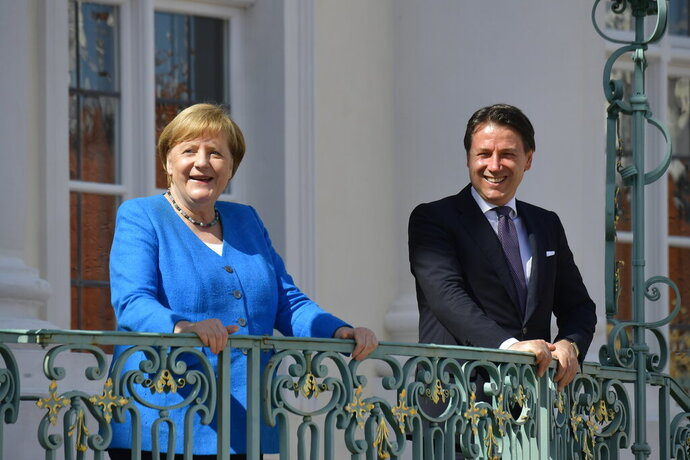 German Chancellor Angela Merkel, left, and Italian Prime Minister Guiseppe Conte, right, talk prior to a meeting at the German government's guest house 'Meseberg' in Gransee, north of Berlin, Germany, Monday, July 13, 2020. (Tobias Schwarz/Pool Photo via AP)