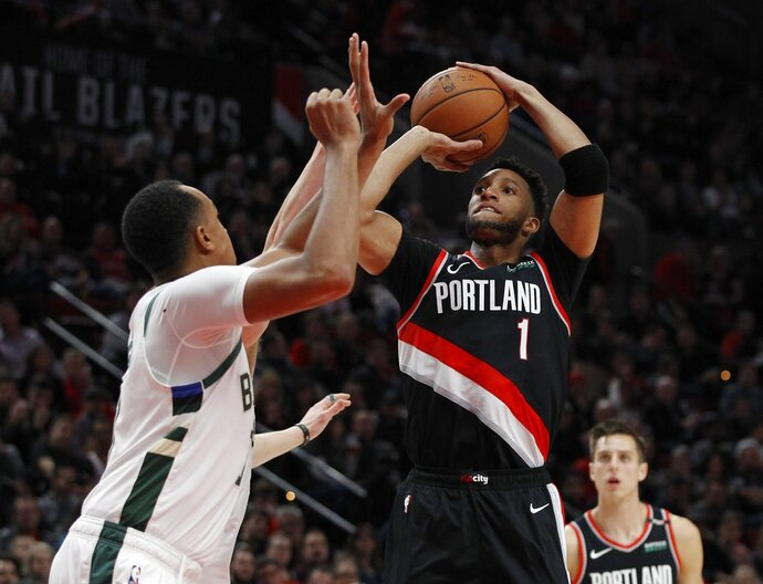 Portland Trail Blazers guard Evan Turner, right, shoots as Milwaukee Bucks forward John Henson, left, defends during the first half of an NBA basketball game in Portland, Ore., Tuesday, Nov. 6, 2018. (AP Photo/Steve Dipaola)