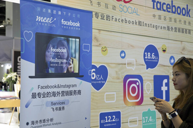 FILE -  In this April 28, 2017, file photo, a foreign social media advertisement like Facebook and Instagram promotes its services during the Global Mobile Internet Conference (GMIC) in Beijing, China. China says its diplomats and government officials will fully exploit foreign social media platforms such as Facebook and Twitter that are blocked off to its own citizens. A foreign ministry spokesman on Monday said their use would improve communication with people outside China and better introduce China's situation and policies. (AP Photo/Ng Han Guan, File)