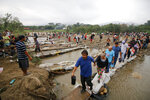 People cross the Tachira River into Colombia near the Simon Bolivar International bridge, which Venezuelan authorities only open to students and the sick, in Cucuta, Colombia, Tuesday, March 12, 2019, on the border with Venezuela. People crossing the river are using makeshift bridges as the water level grows with the approaching rainy season. (AP Photo/Schneyder Mendoza)