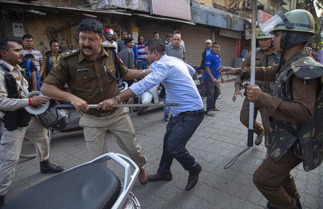 Policemen detain a protestor demonstrating against the Citizenship Amendment Bill (CAB) in Gauhati, India, Wednesday, Dec. 11, 2019. Protesters burned tires and blocked highways and rail tracks in India's remote northeast for a second day Wednesday as the upper house of Parliament began debating legislation that would grant citizenship to persecuted Hindus and other religious minorities from Pakistan, Bangladesh and Afghanistan. (AP Photo/Anupam Nath)