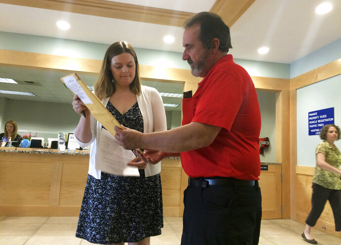 Courier John Campbell, center right, receives election results from City Clerk Angela Holmes, left, Thursday, June 14, 2018, at Westbrook City Hall, in Westbrook, Maine. The results are headed to Augusta, the state capital, for ranked choice voting tabulations. Maine held the first statewide ranked choice voting primary in American history on Tuesday. (AP Photo/Patrick Whittle)