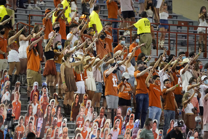 "FILE - In this Saturday, Sept. 12, 2020, file photo, fans join in singing ""The Eyes of Texas"" after Texas defeated UTEP 59-3 in an NCAA college football game in Austin, Texas. Texas athletic director Chris Del Conte said Wednesday, Oct. 14, 2020, he expects players to ""stand together as a unified group"" to show appreciation for the school and fans during the playing of the school song ""The Eyes of Texas"" after games, but didn't say what will happen if they refuse. The song has exploded into a thorny controversy after several football players and other athletes said over the summer they no longer wanted to sing it because of its uncomfortable connections to racist elements of the school's past. (AP Photo/Chuck Burton, File)"