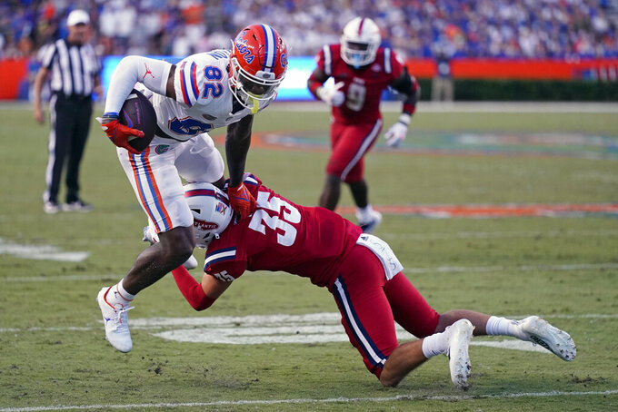 Florida wide receiver Ja'Markis Weston (82) tries to escape a tackle by Florida Atlantic safety Jordan Helm (35) during the first half of an NCAA college football game Saturday, Sept. 4, 2021, in Gainesville, Fla. (AP Photo/John Raoux)