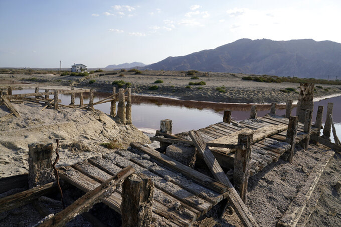A dried up former boating dock is seen along the Salton Sea Wednesday, July 14, 2021, in Desert Shores, Calif. Demand for electric vehicles has shifted investments into high gear to extract lithium from geothermal wastewater around California's dying Salton Sea. The ultralight metal is critical to rechargeable batteries. Despite widespread availability in the United States, Nevada has the country's only lithium plant, and U.S. production lags far behind Australia, Chile, Argentina and China. California's largest but rapidly shrinking lake is at the forefront of efforts to make the U.S. a major global player, though decades of economic stagnation and environmental ruin have left some residents on its receding shores indifferent or wary. (AP Photo/Marcio Jose Sanchez)