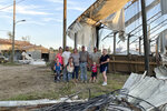Marianne Eachus and her family pose among the debris at Wellacrest Farms in Mullica Hill, N.J. A tornado passes passed through the area on Wednesday, Sept. 1, 2021.(Marianne Eachus via AP)