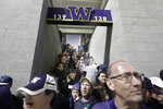 Fans huddle in a stairway at Husky Stadium during a weather delay in the first quarter of an NCAA college football game between Washington and California, Saturday, Sept. 7, 2019, in Seattle. Fans were urged to seek shelter in nearby buildings due to the possibility of severe weather in the area. (AP Photo/Ted S. Warren)