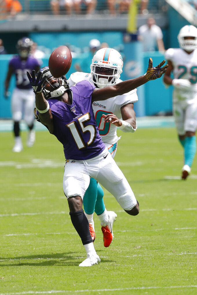 Baltimore Ravens wide receiver Marquise Brown (15) attempts to grab a pass as Miami Dolphins defensive back Chris Lammons (30) defends, during the first half at an NFL football game, Sunday, Sept. 8, 2019, in Miami Gardens, Fla. (AP Photo/Wilfredo Lee)