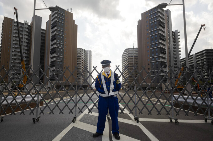 A guard stands in front of a fence to close off a construction site for the athletes' village to be used during the postponed Tokyo 2020 Olympic and Paralympic Games, in Tokyo Thursday, April 8, 2021. Many preparations are still up in the air as organizers try to figure out how to hold the postponed games in the middle of a pandemic. (AP Photo/Hiro Komae)