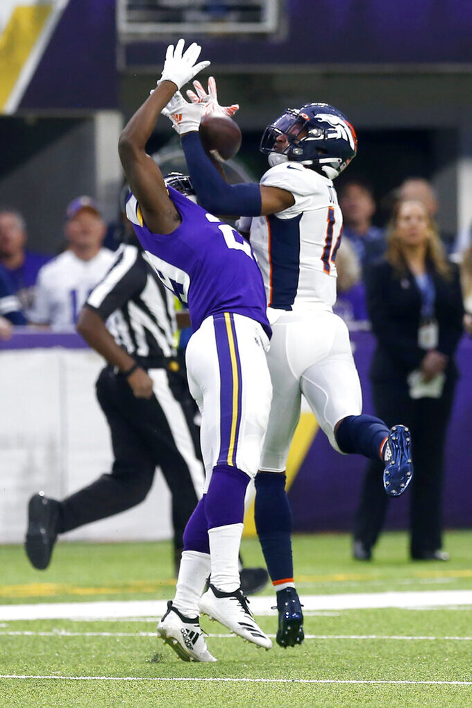 Denver Broncos wide receiver Courtland Sutton, right, catches a pass over Minnesota Vikings cornerback Xavier Rhodes, left, during the first half of an NFL football game, Sunday, Nov. 17, 2019, in Minneapolis. (AP Photo/Jim Mone)