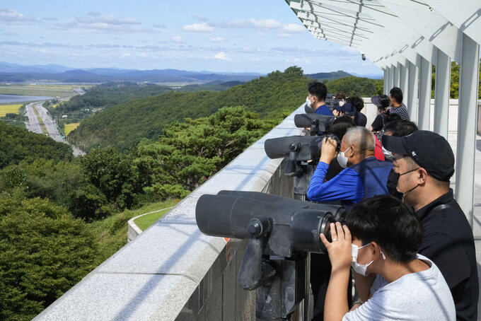 Visitors watch the North Korea side from the Unification Observation Post in Paju, South Korea, near the border with North Korea, Sunday, Sept. 26, 2021. The powerful sister of North Korean leader Kim Jong Un said Saturday that her country will take steps to repair ties with South Korea, and may even discuss another summit between their leaders, if the South drops what she described as hostility and double standards. (AP Photo/Ahn Young-joon)
