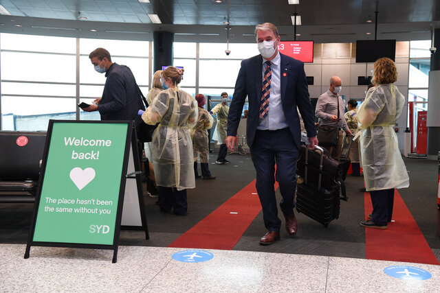 First passengers from Melbourne arrive at Sydney Airport, Australia, Monday, Nov. 23, 2020. Border restrictions were lifted between NSW and Victoria at midnight allowing people coming from Victoria to enter NSW without having to go into 14 day isolation. (Dean Lewins/AAP Image via AP)