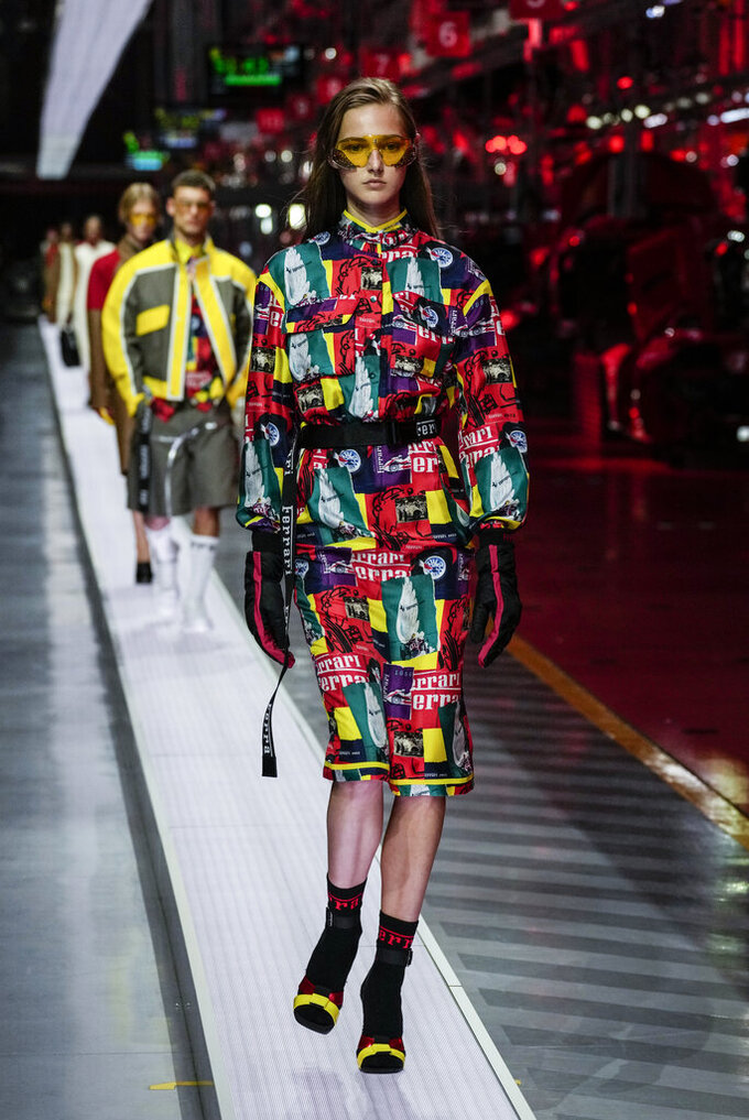 A model wears a creation as part of the Ferrari women's and men's Spring Summer 2022 collection, in Maranello, Italy, Sunday, June 13, 2021. (AP Photo/Antonio Calanni)