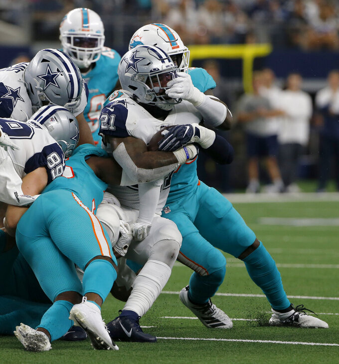 Dallas Cowboys running back Ezekiel Elliott (21) is stopped by Miami Dolphins outside linebacker Jerome Baker, rear in the first half of an NFL football game in Arlington, Texas, Sunday, Sept. 22, 2019. (AP Photo/Michael Ainsworth)