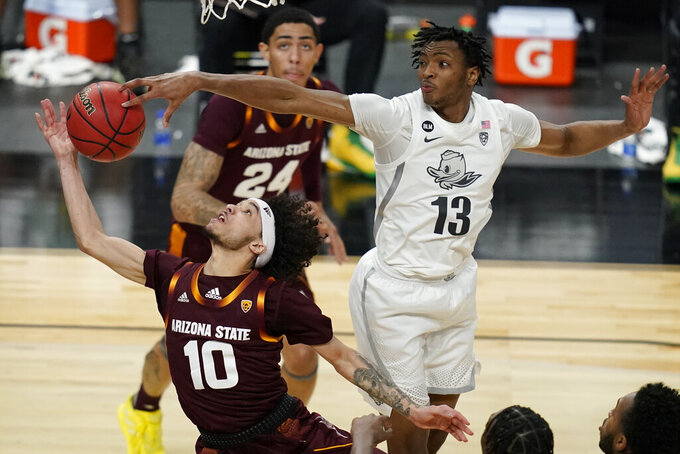 Oregon's Chandler Lawson (13) blocks a shot by Arizona State's Jaelen House (10) during the first half of an NCAA college basketball game in the quarterfinal round of the Pac-12 men's tournament Thursday, March 11, 2021, in Las Vegas. (AP Photo/John Locher)