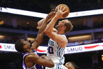 Charlotte Hornets forward Cody Zeller, right, goes up for the shot against Sacramento Kings forward Harrison Barnes, left, during the first quarter of an NBA basketball game in Sacramento, Calif., Wednesday, Oct. 30, 2019. (AP Photo/Rich Pedroncelli)