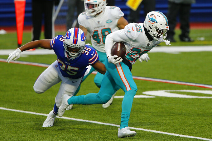 Miami Dolphins cornerback Xavien Howard (25) returns an interception against Buffalo Bills' Antonio Williams (35) in the second half of an NFL football game, Sunday, Jan. 3, 2021, in Orchard Park, N.Y. (AP Photo/John Munson)
