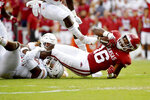Texas defenders Jaylan Ford and Brenden Schooler (14) tackle Arkansas receiver Treylon Burks (16) during the first half of an NCAA college football game Saturday, Sept. 11, 2021, in Fayetteville, Ark. (AP Photo/Michael Woods)