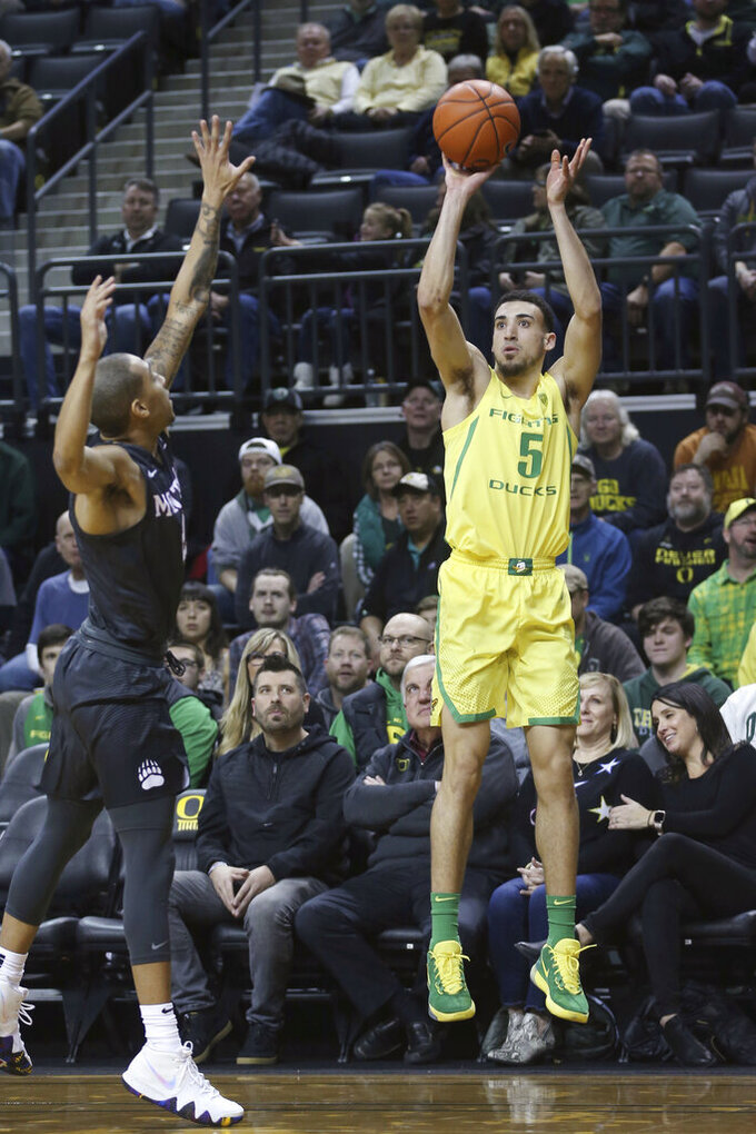 Oregon's Chris Duarte, right, shoots over Montana's Kendal Manuel during the first half of n NCAA college basketball game in Eugene, Ore., Wednesday, Dec. 18, 2019. (AP Photo/Chris Pietsch)