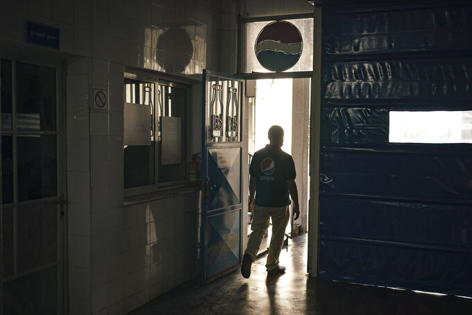 A Palestinian employee walks at the Pepsi bottling plant in Gaza City, Monday, June 21, 2021. Israel on Monday eased some restrictions on the Gaza Strip however the Pepsi factory announced today that it was closing and laying off workers because raw materials needed to stay in business are still not coming. (AP Photo/Felipe Dana)