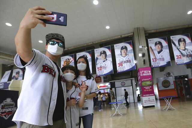 Fans wearing face masks to help protect against the spread of the new coronavirus take a selfie as they arrive to watch the KBO league game between Doosan Bears and LG Twins in Seoul, South Korea, Sunday, July 27, 2020. South Korean Baseball Organization (KBO) on Sunday started admitting fans to the games but only at 10% capacity for each venue.(AP Photo/Ahn Young-joon)