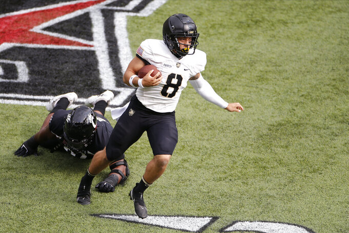Army quarterback Christian Parrish, right, runs past Cincinnati defensive lineman Curtis Brooks during the first half of an NCAA college football game Saturday, Sept. 26, 2020, in Cincinnati, Ohio. (AP Photo/Jay LaPrete)