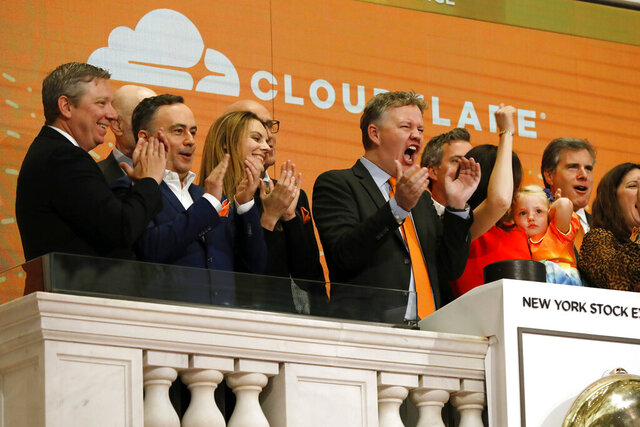 FILE - In this Sept. 13, 2019, file photo, Cloudflare co-founder and CEO Matthew Prince, right center, applauds during New York Stock Exchange opening bell ceremonies to celebrate his company's IPO. San Francisco-based Cloudflare said Wednesday, Jan. 15, 2020, it will provide free cybersecurity support to federal election campaigns. (AP Photo/Richard Drew, File)