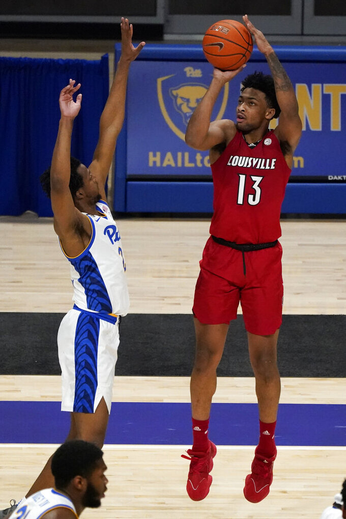 Louisville's David Johnson (13) shoots as Pittsburgh's Femi Odukale (2) defends during the second half of an NCAA college basketball game, Tuesday, Dec. 22, 2020, in Pittsburgh. (AP Photo/Keith Srakocic)