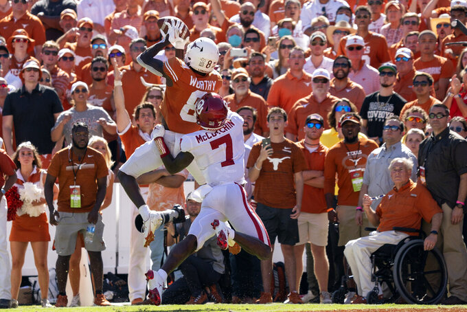 Texas wide receiver Xavier Worthy (8) pulls in a touchdown pass in front of a sea of Texas fans including Texas Gov. Greg Abbott, bottom right, as Oklahoma cornerback Latrell McCutchin (7) defends during the fourth quarter of an NCAA college football game at the Cotton Bowl, Saturday, Oct. 9, 2021, in Dallas. Oklahoma won 54-48. (AP Photo/Jeffrey McWhorter)