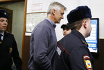 Founder of the Baring Vostok investment fund Michael Calvey, centre, is escorted to the court room in Moscow, Russia, Friday, Feb. 15, 2019. A veteran U.S. investment fund manager has been detained in Moscow and faces fraud charges. A Moscow court said on Friday that Michael Calvey, founder and senior partner at Baring Vostok equity firm, was detained alongside two other fund managers. (AP Photo/Alexander Zemlianichenko)