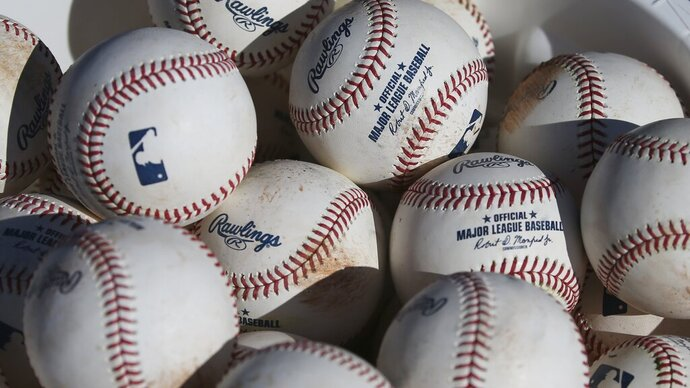 "FILE - In this Feb. 14, 2020, file photo, baseballs occupy a bucket after use during fielding practice during spring training baseball workouts for pitchers and catchers at Cleveland Indians camp in Avondale, Ariz. Major League Baseball is suspending all political contributions in the wake of last week's invasion of the U.S. Capitol by a mob loyal to President Donald Trump, joining a wave of major corporations rethinking their efforts to lobby Washington. ""In light of the unprecedented events last week at the U.S. Capitol, MLB is suspending contributions from its Political Action Committee pending a review of our political contribution policy going forward,"" the league said in a statement to The Associated Press on Wednesday, Jan. 13, 2021. (AP Photo/Ross D. Franklin, File)"