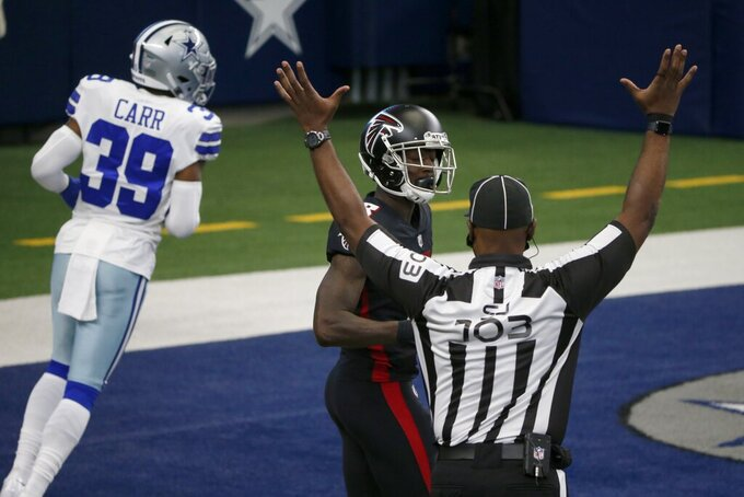 Field judge Eugene Hall (103) signals after Atlanta Falcons' Calvin Ridley, center rear, scored a touchdown after catching a pass as Dallas Cowboys cornerback Brandon Carr (39) jogs past in the first half of an NFL football game in Arlington, Texas, Sunday, Sept. 20, 2020. (AP Photo/Michael Ainsworth)