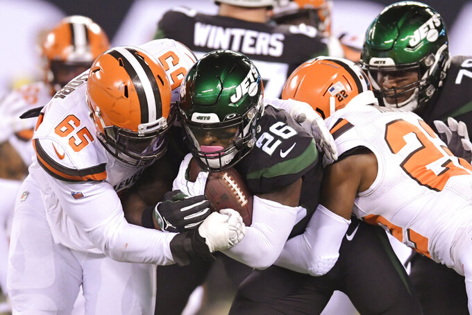Cleveland Browns' Larry Ogunjobi (65) and Eric Murray (22) tackle New York Jets' Le'Veon Bell (26) during the first half of an NFL football game Monday, Sept. 16, 2019, in East Rutherford, N.J. (AP Photo/Bill Kostroun)