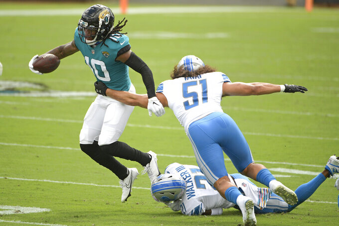 Jacksonville Jaguars wide receiver Laviska Shenault Jr., left, tries to avoid a tackle by Detroit Lions linebacker Jahlani Tavai (51) and safety Tracy Walker (21) during the first half of an NFL football game, Sunday, Oct. 18, 2020, in Jacksonville, Fla. (AP Photo/Phelan M. Ebenhack)