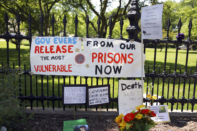 """Signs and posters are left outside the Wisconsin governor's mansion in Maple Bluff, Wis., on June 18, 2020, as part of a """"Drive to Decarcerate"""" event. Those attending urged Gov. Tony Evers to release inmates from Wisconsin's overcrowded prisons to slow the spread of COVID-19. Before the pandemic, Evers set a goal to cut the state's prison population in half. But 23 state prisons still exceed their designed capacity. (Coburn Dukehart/Wisconsin Watch via AP)"""