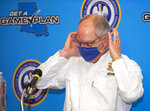 """Louisiana Gov. John Bel Edwards puts his face mask back on at the conclusion of a press conference at Louisiana State Police Training Academy, Thursday, Sept. 10, 2020, in Baton Rouge, La. Edwards says the state will ease various restrictions on public gatherings aimed at preventing the spread of COVID-19 — but he's withholding details for a day. Edwards said Thursday that Louisiana will move to """"Phase Three"""" of restrictions after current restrictions expire Friday. (Travis Spradling/The Advocate via AP)"""