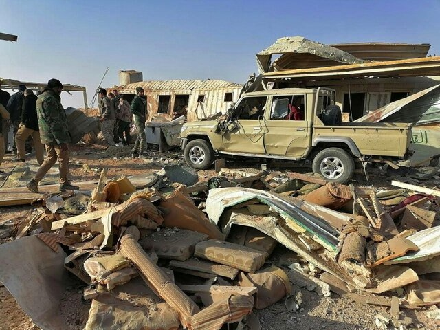 Fighters from the Kataeb Hezbollah, or Hezbollah Brigades militia, inspect the destruction at their headquarters in the aftermath of a U.S. airstrike in Qaim, Iraq, Monday, Dec. 30, 2019. The Iranian-backed militia said Monday that the death toll from U.S. military strikes in Iraq and Syria against its fighters has risen to 25, vowing to exact revenge for the