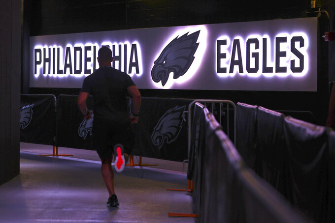 FILE - In this Thursday, Aug. 19, 2021, file photo, a Philadelphia Eagles' player runs back to the locker room before a preseason NFL football game against the New England Patriots in Philadelphia. The NFL has mandated that only fully vaccinated personnel, with a maximum of 50 people, will have access to locker rooms while players are present on game days. Players are not required to be vaccinated against COVID-19, but the NFL has reported that more than 90% of them are. (AP Photo/Rich Schultz, File)