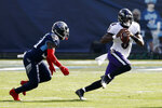 Baltimore Ravens quarterback Lamar Jackson (8) scrambles away from Tennessee Titans cornerback Desmond King, left, in the first half of an NFL wild-card playoff football game Sunday, Jan. 10, 2021, in Nashville, Tenn. (AP Photo/Wade Payne)