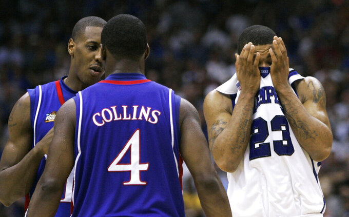 FILE - In this April 7, 2008, file photo, Memphis' Derrick Rose (23) covers his face in front of Kansas' Sherron Collins (4) and Mario Chalmers, left, late in the overtime period of the championship game at the NCAA college basketball Final Four in San Antonio. Kansas won 75-68. (AP Photo/Eric Gay, FIle)