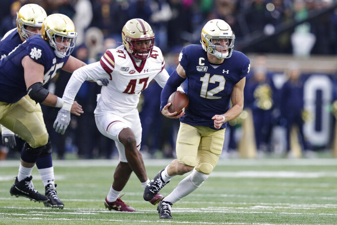 Notre Dame quarterback Ian Book (12) scrambles away from Boston College defensive end Shitta Sillah (47) during the first half of an NCAA college football game in South Bend, Ind., Saturday, Nov. 23, 2019. (AP Photo/Michael Conroy)