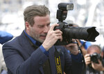 Actor John Travolta takes a picture with a press photographers camera during the photo call for the film 'Gotti' at the 71st international film festival, Cannes, southern France, Tuesday, May 15, 2018. (Photo by Joel C Ryan/Invision/AP)